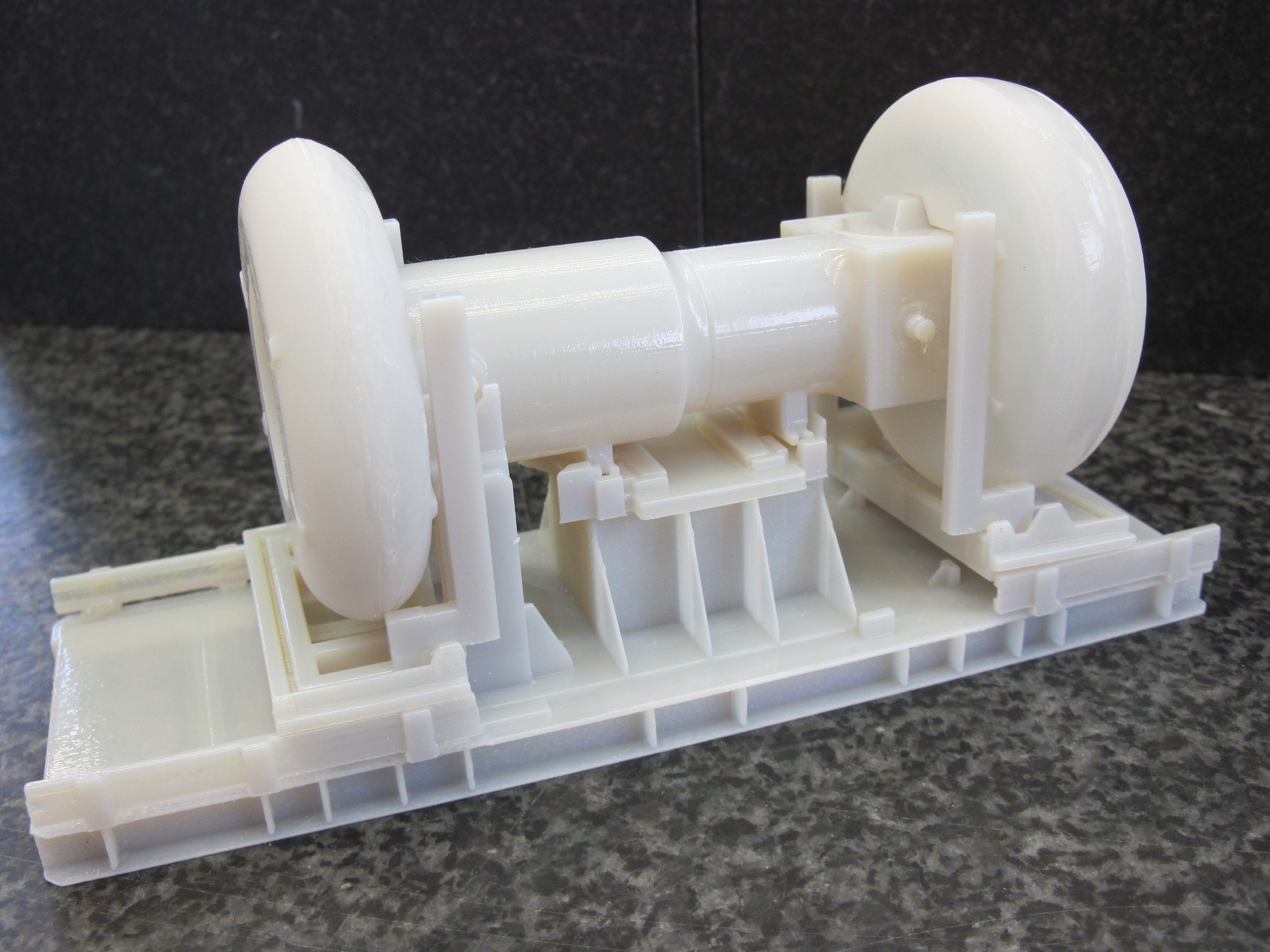 White plastic component somewhat similar to a sewing machine in shape, on an integral base, with various connectors and flanges all part of the same unit.