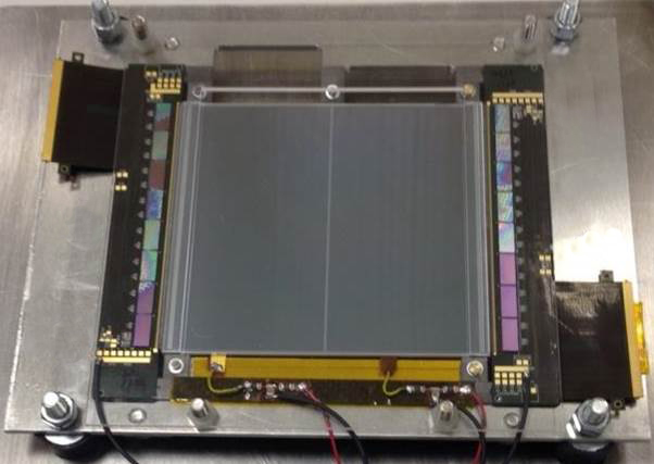 A top view of a prototype module containing 16 CBC integrated circuits connected either side of 4 silicon strip detectors, of which only the top 2 detectors are visible.
